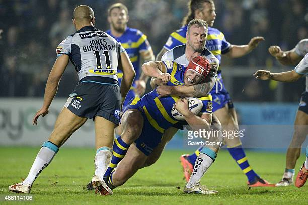Chris Hill of Warrington Wolves is tackled by Jamie Peacock of Leeds Rhinos during the First Utility Super League match between Warrington Wolves and...
