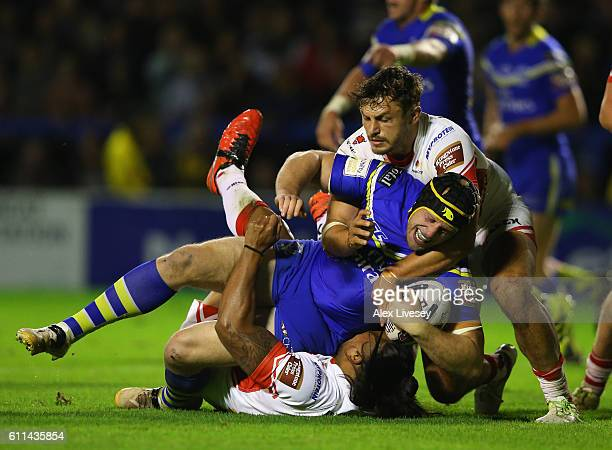 Chris Hill of Warrington Wolves is tackled by Jon Wilkin and Atelea Vea of St Helens during the First Utility Super League Semi Final match between...