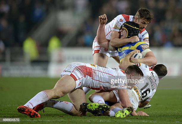 Chris Hill of Warrington Wolves is tackled by Jon Wilkin Lance Hohaia and Joe Greenwood of St Helens during the First Utility Super League match...