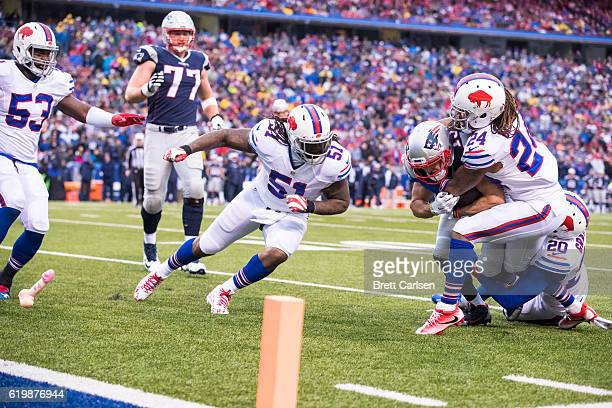 Chris Hogan of the New England Patriots fights for yards while being tackled by Corey Graham and Stephon Gilmore of the Buffalo Bills as a foreign...