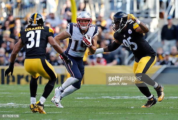 Chris Hogan of the New England Patriots runs between Ross Cockrell and Jarvis Jones of the Pittsburgh Steelers after making a catch in the first...