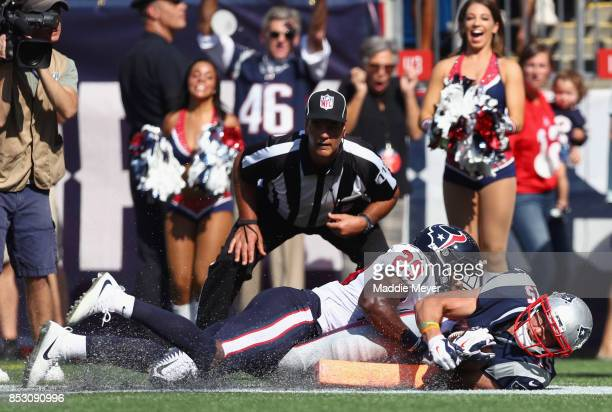 Chris Hogan of the New England Patriots scores a touchdown as he is tackled by Andrew Hal of the Houston Texans during the second quarter of a game...