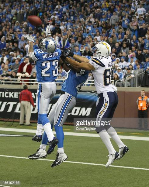 Chris Houston of the Detroit Lions intercepts a pass next to teammate Chris Harris and in front of Vincent Jackson of the San Diego Chargers during a...