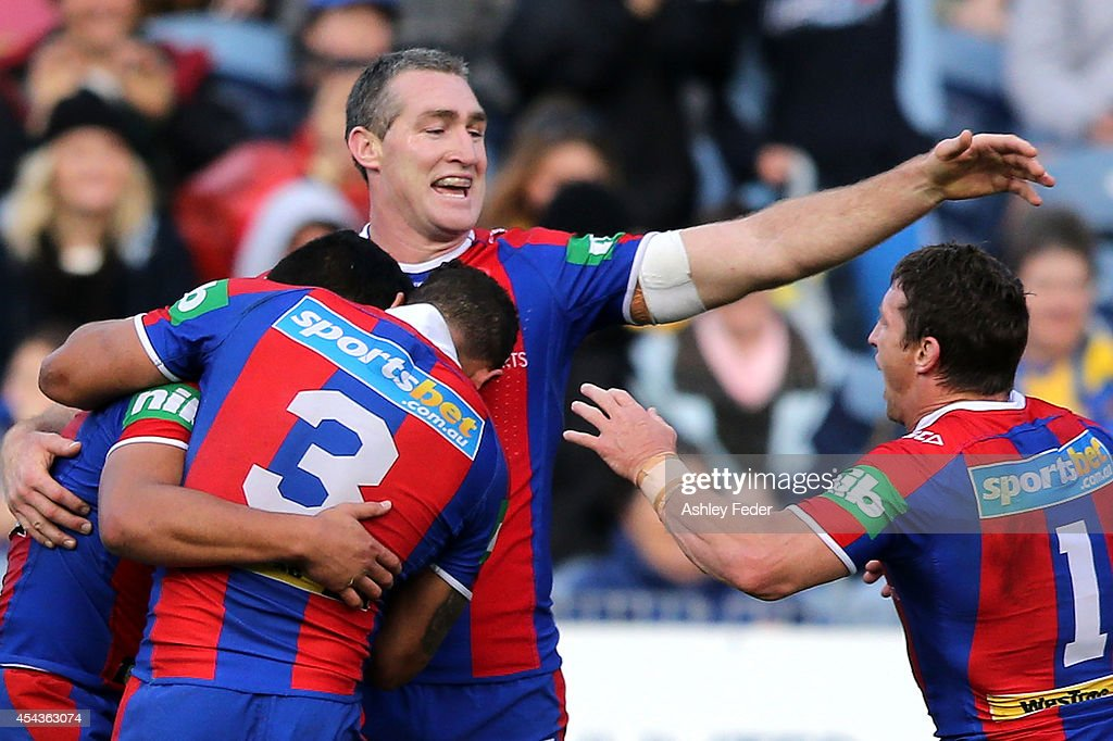 Chris Houston of the Knights celebrates a try with teammates during the round 25 NRL match between the Newcastle Knights and the Parramatta Eels at Hunter Stadium on August 30, 2014 in Newcastle, Australia.