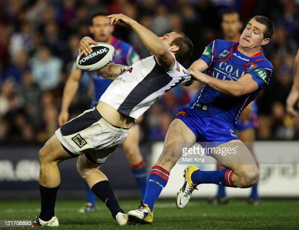 Chris Houston of the Knights tackles Scott Anderson of the Broncos around the collar during the round 24 NRL match between the Newcastle Knights and...