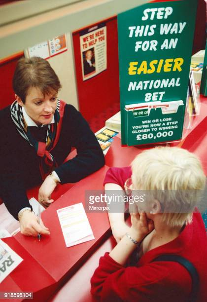 Chris Hudson, mangers of Ladbrokes in the Bigg Market, gives out last minute tips to Grand National Punter Emma Walker, 2nd April 1997.