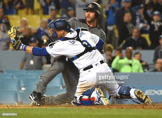 Chris Iannetta of the Arizona Diamondbacks is called safe as he beats the tag by Yasmani Grandal of the Los Angeles Dodgers on a single by Chris...