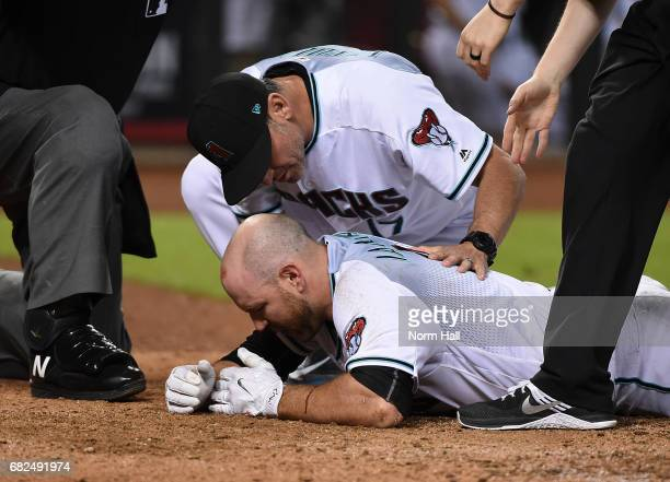 Chris Iannetta of the Arizona Diamondbacks is looked at by manager Torey Lovullo after getting hit in the face with a pitch by Johnny Barbato of the...
