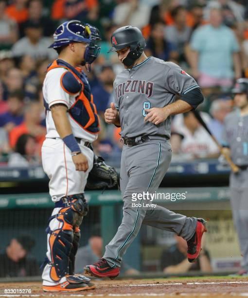 Chris Iannetta of the Arizona Diamondbacks scores in rthe third inning on a double by Brandon Drury as Juan Centeno of the Houston Astros looks on at...