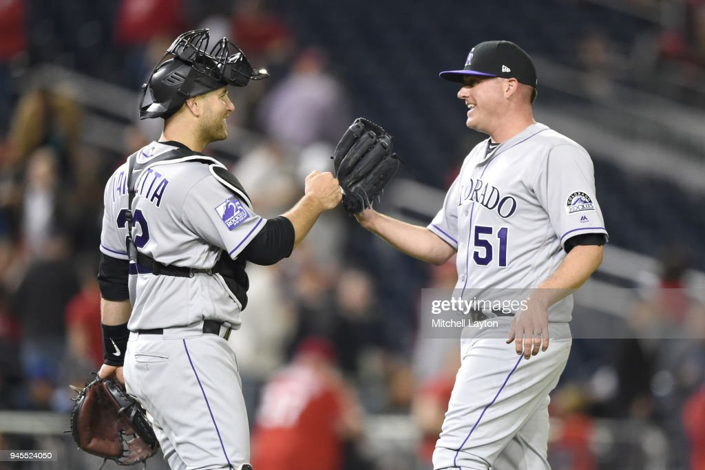 Chris Iannetta #22 of the Colorado Rockies and Jake McGee #51 celebrate a win after a baseball game against the Washington Nationals at Nationals Park on April 12, 2018 in Washington, DC.
