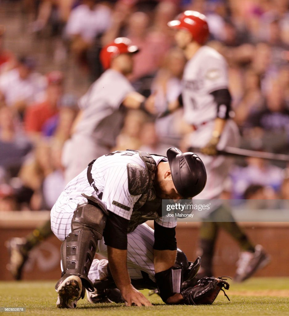 Chris Iannetta #22 of the Colorado Rockies kneels as Jose Peraza #9 of the Cincinnati Reds and Joey Votto #19 of the Cincinnati Reds celebrate Peraza's scoring on a wild pitch in the seventh inning at Coors Field on May 26, 2018 in Denver, Colorado.