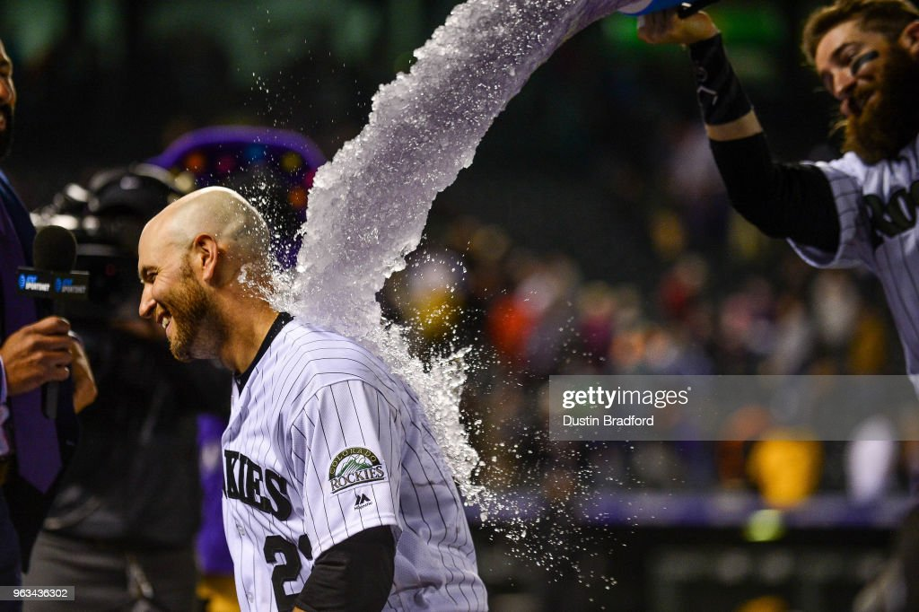 Chris Iannetta #22 of the Colorado Rockies receives an ice bath from Charlie Blackmon #19 of the Colorado Rockies after hitting a 10th inning walk-off single against the San Francisco Giants at Coors Field on May 28, 2018 in Denver, Colorado.