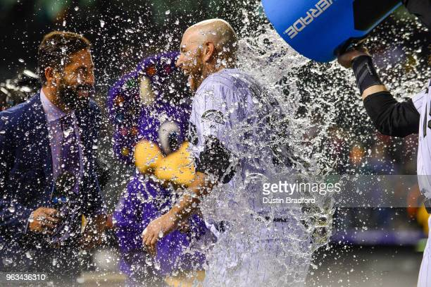Chris Iannetta of the Colorado Rockies receives an ice bath from Charlie Blackmon of the Colorado Rockies after hitting a 10th inning walkoff single...