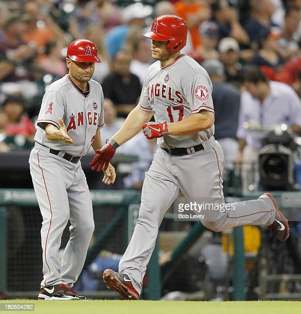 Chris Iannetta of the Los Angeles Angels of Anaheim receives congratulations from third base coach Dino Ebel of the Los Angeles Angels of Anaheim...