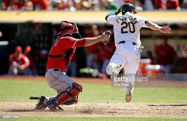 Chris Iannetta of the Los Angeles Angels of Anaheim tags out a diving Josh Donaldson of the Oakland Athletics in the fourth inning at Oco Coliseum on...