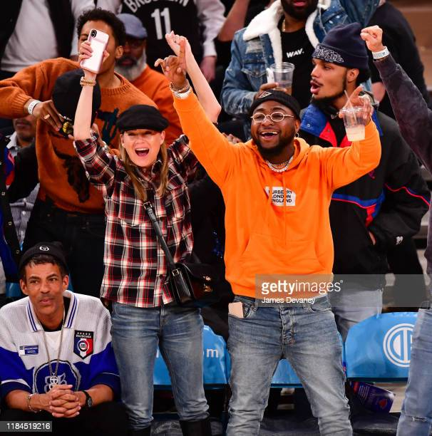 Chris Ivery Ellen Pompeo and Davido Adeleke attend the Brooklyn Nets v New York Knicks game at Madison Square Garden on November 24 2019 in New York...