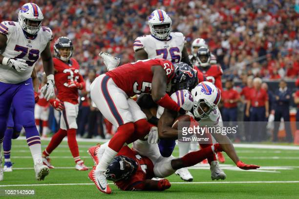 Chris Ivory of the Buffalo Bills is tackled for a loss in the third quarter by Whitney Mercilus of the Houston Texans and Zach Cunningham at NRG...