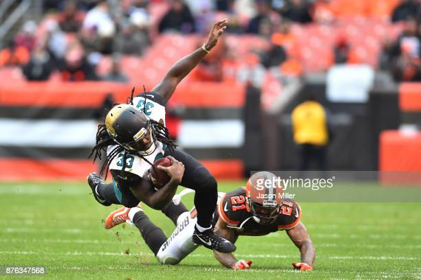 Chris Ivory of the Jacksonville Jaguars dives over Jamar Taylor of the Cleveland Browns in the second half at FirstEnergy Stadium on November 19,...