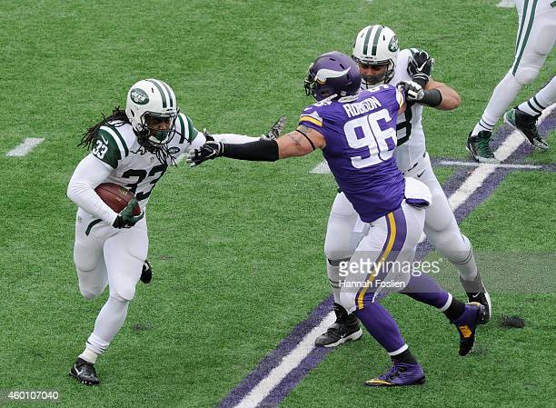 Chris Ivory of the New York Jets carries the ball past teammate Breno Giacomini of the New York Jets blocking Brian Robison of the Minnesota Vikings...
