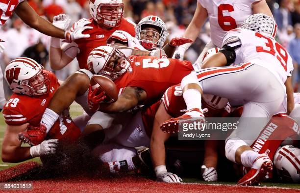 Chris James of the Wisconsin Badgers reaches for a touchdown against the Ohio State Buckeyes in the Big Ten Championship at Lucas Oil Stadium on...