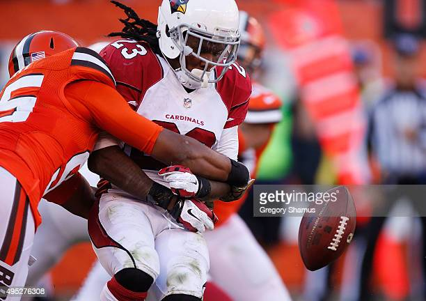 Chris Johnson of the Arizona Cardinals fumbles during a third quarter run while being hit by Armonty Bryant of the Cleveland Browns at FirstEnergy...