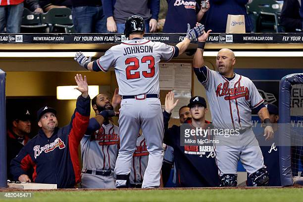 Chris Johnson of the Atlanta Braves celebrates outside the Braves dugout after hitting a solo home run off of Matt Garza of the Milwaukee Brewers in...