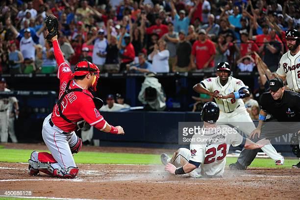 Chris Johnson of the Atlanta Braves is tagged out at home in the 6th inning by Hank Conger of the Los Angeles Angels of Anaheim at Turner Field on...
