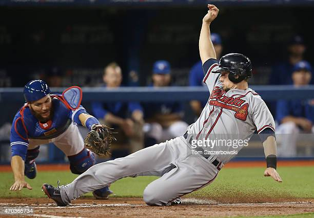 Chris Johnson of the Atlanta Braves slides across home plate safely to score a run on a sacrifice fly in the third inning during MLB game action as...