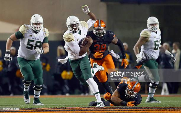 Chris Johnson of the Baylor Bears carries the ball against Trace Clark of the Oklahoma State Cowboys and Emmanuel Ogbah of the Oklahoma State Cowboys...