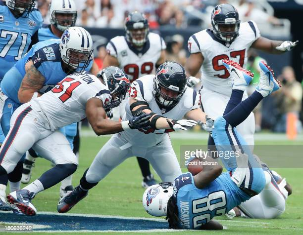 Chris Johnson of the Tennessee Titans is tackled by a group of Houston Texans at Reliant Stadium on September 15 2013 in Houston Texas