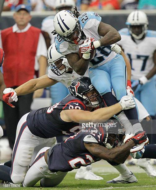 Chris Johnson of the Tennessee Titans is tackled by J.J. Watt of the Houston Texans and Johnathan Joseph of the Houston Texans at Reliant Arena at...