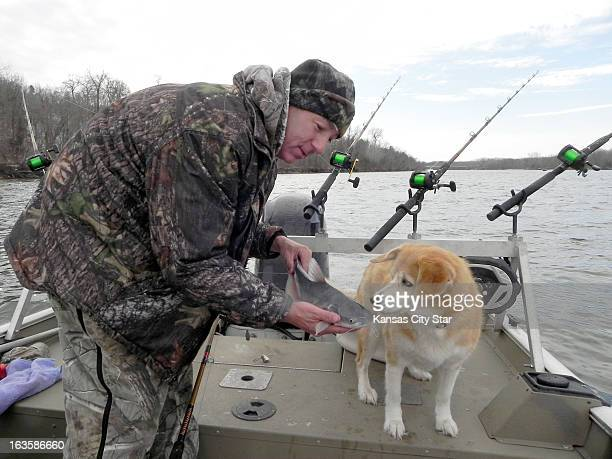 Chris Jones' fishing dog Angel sniffs a small blue catfish caught on the upper end of Lake of the Ozarks