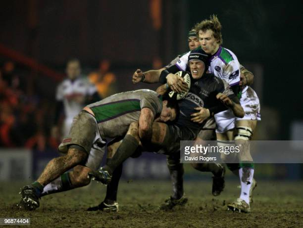 Chris Jones of Sale is tackled by Mike MacDonald and Kearnan Myall during the Guinness Premiership match between Sale Sharks and Leeds Carnegie at...