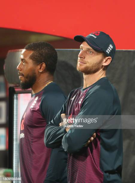 Chris Jordan and Jos Buttler of England look on during the 3rd One Day International match between India and England at MCA Stadium on March 28, 2021...