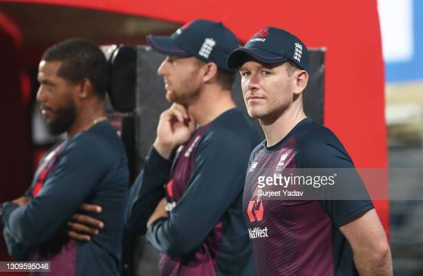 Chris Jordan, Jos Buttler and Eoin Morgan of England look on during the 3rd One Day International match between India and England at MCA Stadium on...