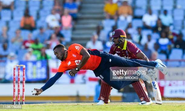 Chris Jordan of England takes the catch to dismiss Darren Bravo of the West Indies as Nicholas Pooran looks on during a T20 match between the West...