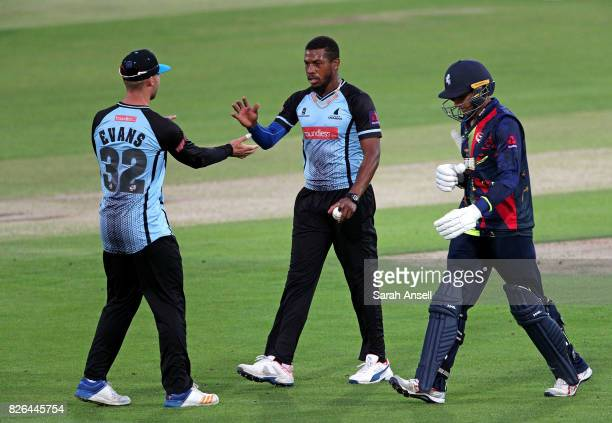 Chris Jordan of Sussex Sharks is congratulated by teammate Laurie Evans after taking the wicket of Imran Qayyum of Kent Spitfires during the match...