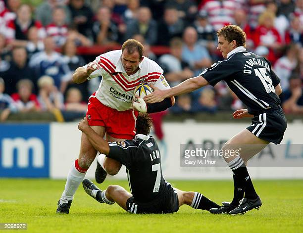Chris Joynt of St Helens is tackled by Adrian Lam and Sean O'Loughlin of Wigan Warriors during the Tetleys Super League match between St Helens and...