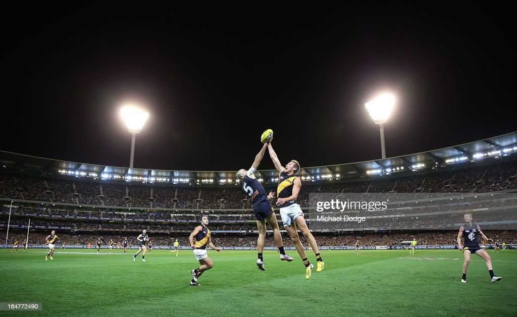 A Chris Judd (L) of the Blues contests for the ball against Luke McGuane of the Tigers during the round one AFL match between the Carlton Blues and the Richmond Tigers at Melbourne Cricket Ground on March 28, 2013 in Melbourne, Australia.