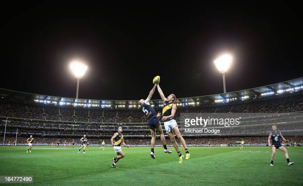 Chris Judd of the Blues contests for the ball against Luke McGuane of the Tigers during the round one AFL match between the Carlton Blues and the...