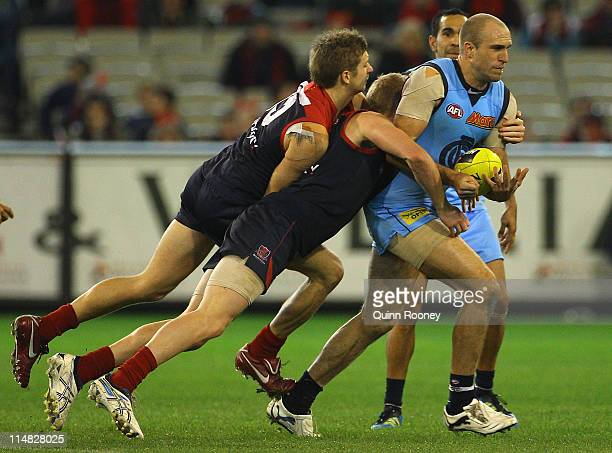 Chris Judd of the Blues handballs whilst being tackled by Ricky Petterd and Jordie McKenzie of the Demons during the round 10 AFL match between the...