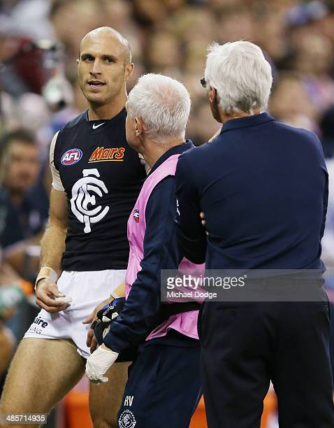 Chris Judd of the Blues speaks to coach Michael Malthouse after limping off the ground with a leg injury only minutes after entering the field as a...