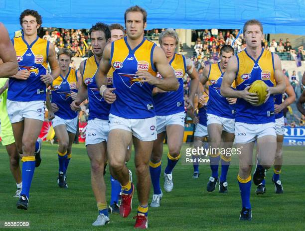 Chris Judd of the Eagles leads the team through the banner at the start of the round three 'Western Derby' AFL match between the West Coast Eagles...
