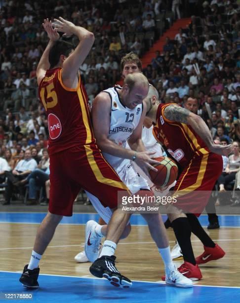 Chris Kaman of Germany drives against Predrag Samardjiski and Pero Antic of Macedonia during a international Basketball Friendly between Germany and...