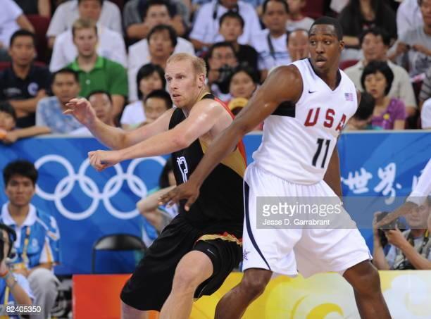 Chris Kaman of Germany looks for the ball against Dwight Howard of the U.S. Men's Senior National Team during the men's group B basketball...