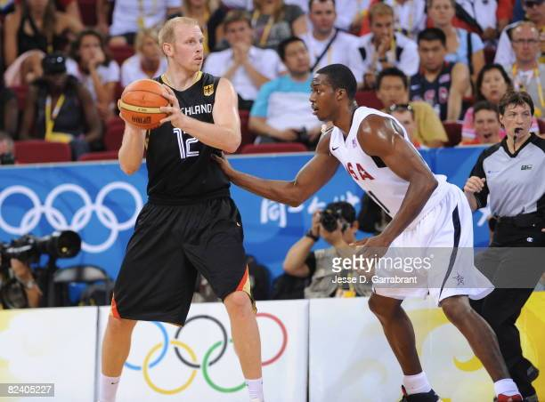 Chris Kaman of Germany looks to pass against Dwight Howard of the U.S. Men's Senior National Team during the men's group B basketball preliminaries...