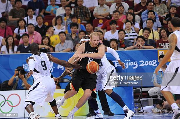 Chris Kaman of Germany passes the ball against Carmelo Anthony of the U.S. Men's Senior National Team during the men's group B basketball...