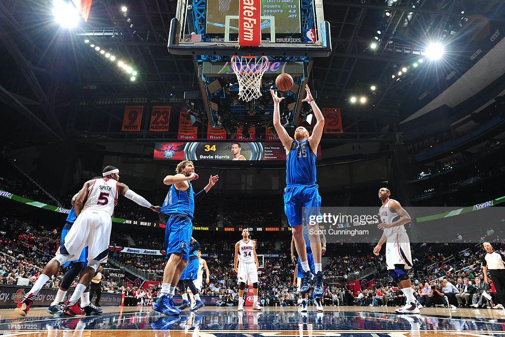 Chris Kaman #35 of the Dallas Mavericks grabs a rebound against the Atlanta Hawks on March 18, 2013 at Philips Arena in Atlanta, Georgia.