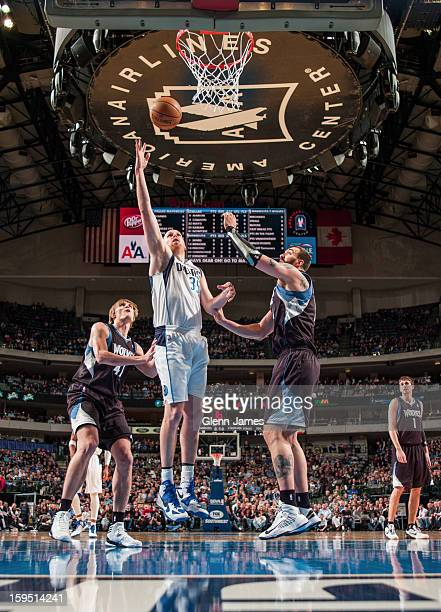 Chris Kaman of the Dallas Mavericks shoots a layup against Nikola Pekovic and Andrei Kirilenko of the Minnesota Timberwolves on January 14 2013 at...