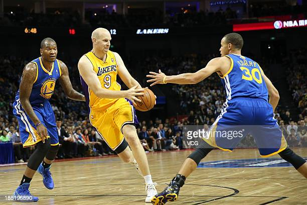 Chris Kaman of the Los Angeles Lakers drives the ball against Marreese Speights and Stephen Curry of the Golden State Warriors during the 2013 Global...